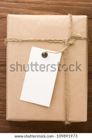 paper parcel wrapped tied with price tag on wood background - stock photo