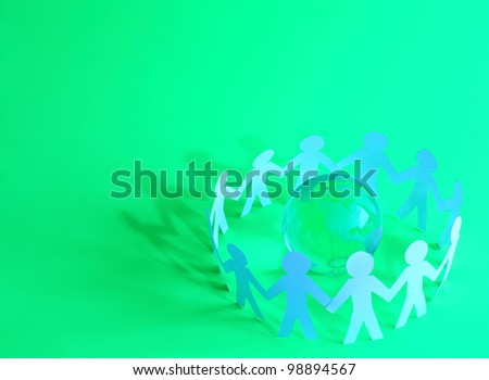 Paper people standing in a circle around glass globe - stock photo