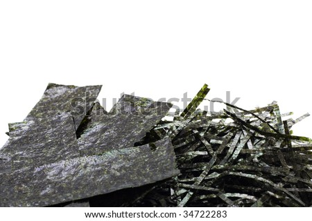 Paper-pieces and shreds of seasoned and dried seaweed, isolated on white with copyspace at the top - stock photo
