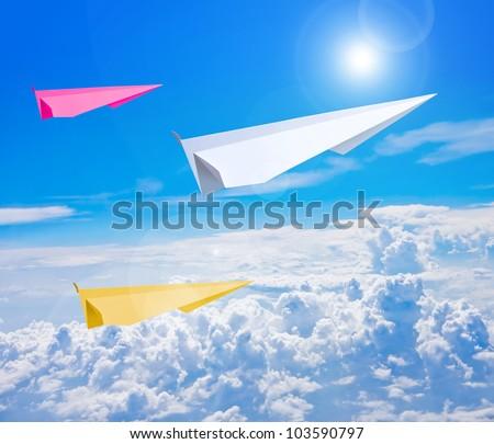 Paper plane flying against blue sky - stock photo