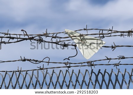 paper plane made of a visa document gets stuck in barbed wire, blue sky and copy space - stock photo