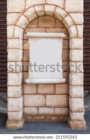 Paper scroll on the brick wall. Ready for your text or sign - stock photo