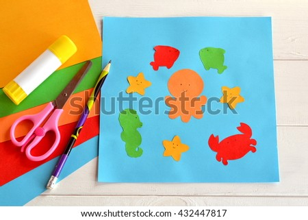 Paper sea animals on blue card. Children applique pattern. Children application. Glue stick, scissors, pencil, colored paper. Preschool and kindergarten paper crafts. DIY project.Kindergarten activity - stock photo