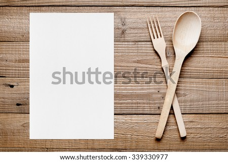 Paper sheet and wooden fork and spoon on table top view - stock photo