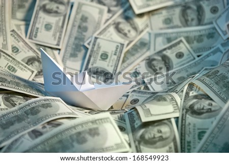 Paper ship at sea of money / studio photography of american moneys of hundred dollar on background  - stock photo