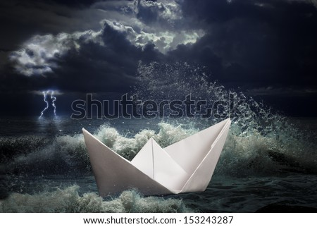 paper ship in storm concept - stock photo