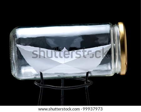 Paper ship in the jar on a black background. - stock photo