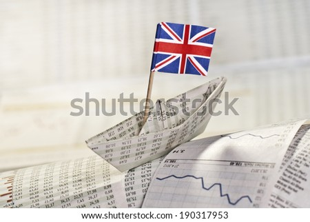 Paper ship with British flag on stock market news. - stock photo