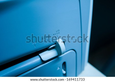 Paper size signs on a modern printer scanner fax device A4, A5, B5, Exec, Ltr, Lgl. Blue technological mood color cast. - stock photo