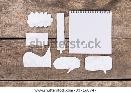 Paper speech bubbles on wooden background - stock photo