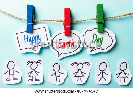 Paper speech bubbles with text Happy Earth Day hanging on the line with some paper people under. - stock photo