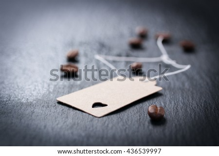 Paper tag with heart on a dark stone background with coffee on a background, closeup - stock photo