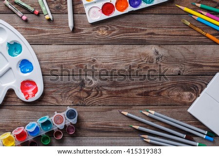 Paper, watercolors, paint brush and some art stuff on wooden   table - stock photo