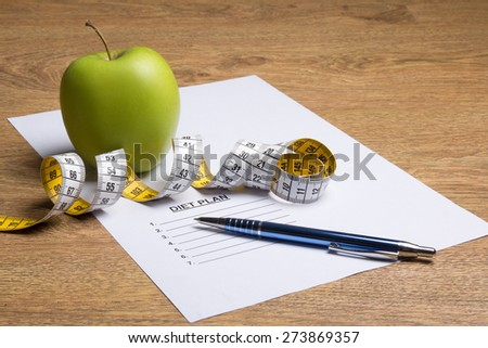 paper with diet plan, pen, apple and measure tape on wooden table - stock photo