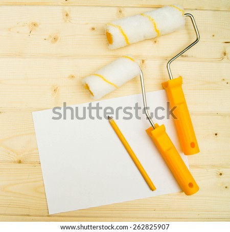 Paper with pencil and platen for paint on wooden background.  - stock photo