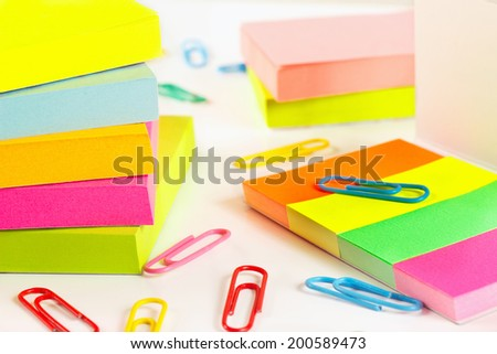 Paperclips and multicolored stickers on white desktop close up - stock photo