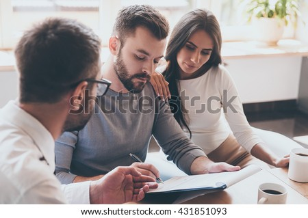 Paperwork before deal. Confident young man signing some document while sitting together with his wife and man in shirt and tie  - stock photo