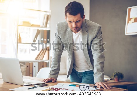 Paperwork everyday. Handsome pensive young man looking at charts while leaning to the table at his working place  - stock photo