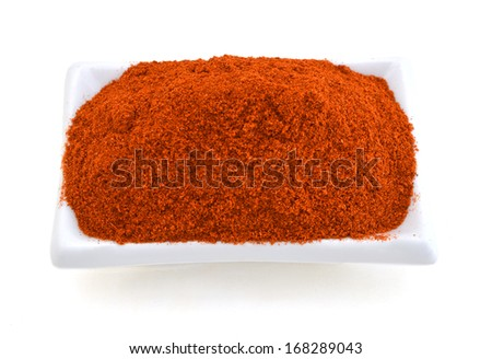 Paprika ground in a white bowl on white background. Used to color rices, stews, and soups, meats.  - stock photo