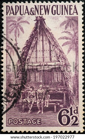 PAPUA NEW GUINEA - CIRCA 1952: A used postage stamp from Papua New Guinea illustrating an indigenous building, issued in 1952. - stock photo