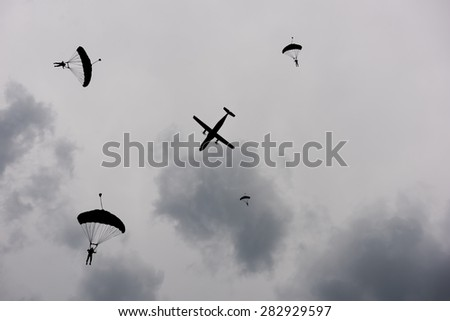 Parachute and plane at dusk sky silhouetted - stock photo