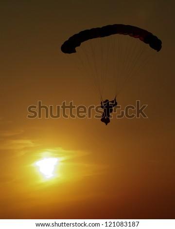 Parachute at sunset - stock photo