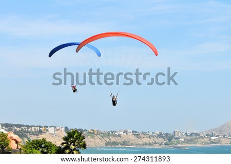 Parachutes flying by the ocean on a sunny day in Lima, Peru - stock photo