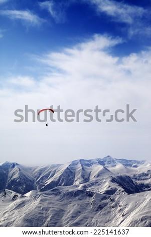 Parachutist silhouette of mountains in windy sky. Caucasus Mountains. Georgia, ski resort Gudauri. - stock photo