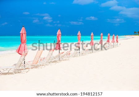Paradise view of tropical empty sandy plage with umbrella and beach chair - stock photo