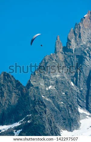 Paraglide over Alps cliff - stock photo