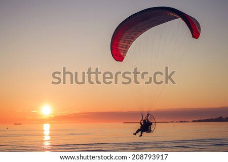 Paraglide silhouette at sea sunset - stock photo