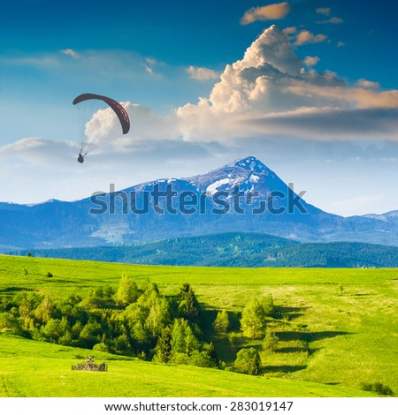 Paraglide silhouette flying over Carpathian spring mountain valley. Majestic landscape with beautiful red clouds above the high mountains  - stock photo
