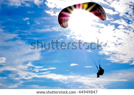 Paraglider against sun on blue sky - stock photo