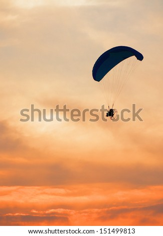 Paraglider - Feeling free on the sunset sky - stock photo
