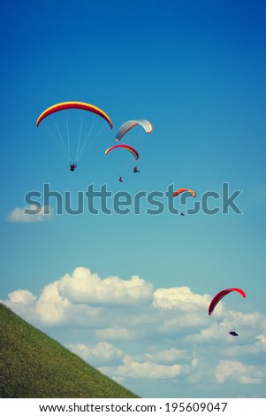 Paraglider flying against the czech central mountains - stock photo