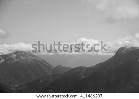 Paraglider flying over Alps mountains. Annecy lake area (Haute-Savoie, France). Aged photo. Black and white. - stock photo