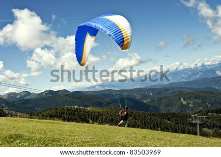 Paraglider flying over the Alps of Trentino - stock photo