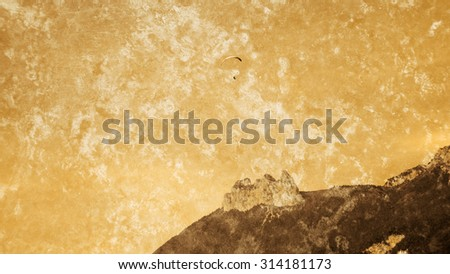 Paraglider flying over the mountains of Savoy at Annecy Lake (France) . Power of nature idea. Retro aged photo with scratches. - stock photo