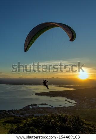 Paraglider flying over vespers Petropavlovsk-Kamchatsky on the background of the Avachinsky bay at sunset - Kamchatka, Russia - stock photo