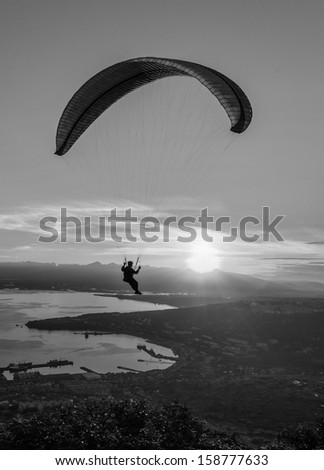 Paraglider flying over vespers Petropavlovsk-Kamchatsky on the background of the Avachinsky bay at sunset - Kamchatka, Russia (black and white) - stock photo