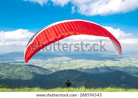 Paraglider in starting phase in front of the mountains. - stock photo