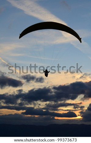 Paraglider in the cloudy sunset sky - stock photo