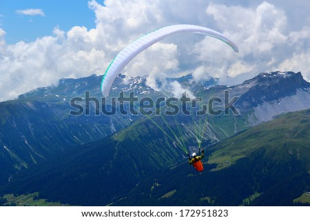 Paraglider is flying in front of mountain landscape of Swiss Alps, Jacobshorn, Davos, Switzerland - stock photo