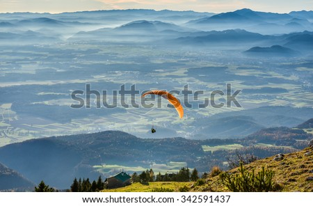 Paraglider is flying in the valley. Paragliding from the mountain with perfect view - stock photo