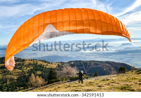 Paraglider is starting  to start his flight. Looking at beautiful valley below with clouds and mist. - stock photo