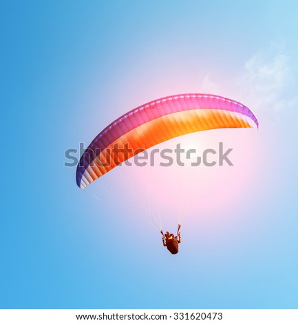 paraglider on the blue sky - stock photo