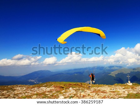 Paraglider prepareing to take off from a mountain - stock photo