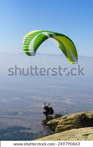 Paraglider preparing to take off from a mountain - stock photo