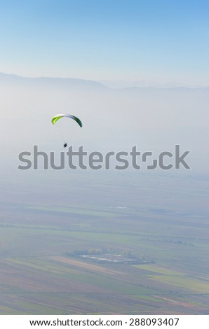 Paraglider silhouette over mountains. Extreme sport stock photo - stock photo