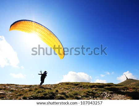 Paraglider taking off from a mountain - stock photo